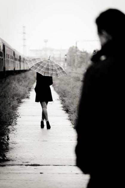 Woman-walking-away-from-man umbrella